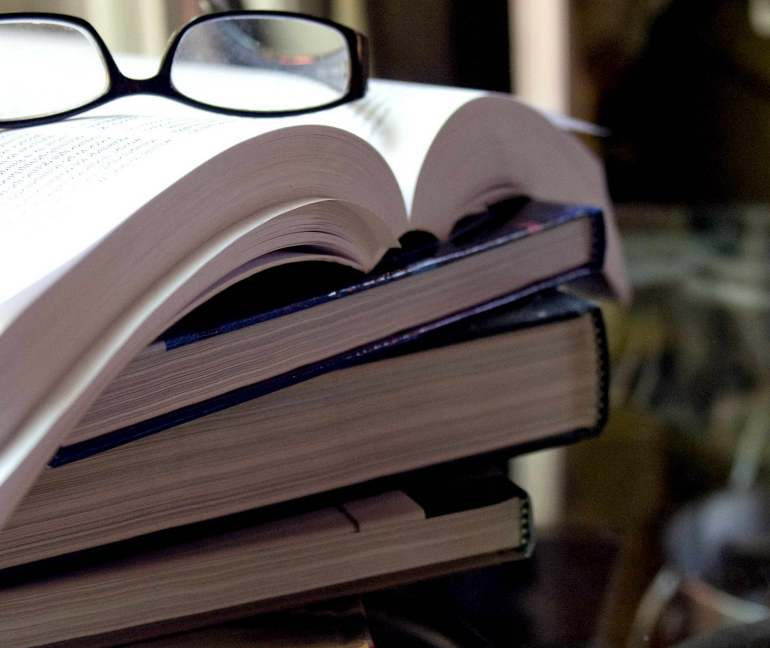 Stack of books topped by pair of eyeglasses